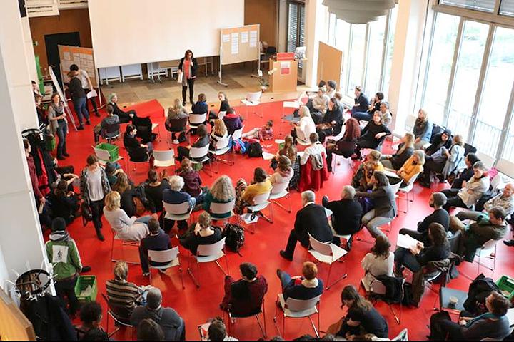 Das Audimax der ASH Berlin von oben: etwa 30 Personen sitzen im Saal, eine Moderatorin auf der Bühne scheint eine Diskussion zu leiten.