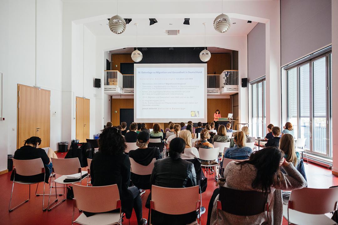 Blick von hinten in das Audimax (großer Vorlesesaal), Vorlesung einer Professorin vor ca. 50 Studierenden