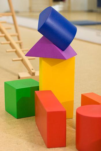 Schaumstoffklötze in verschiedenen Formen bilden zusammen mit einer horizontal aufgestellten Holzleiter eine Parcoursstrecke.