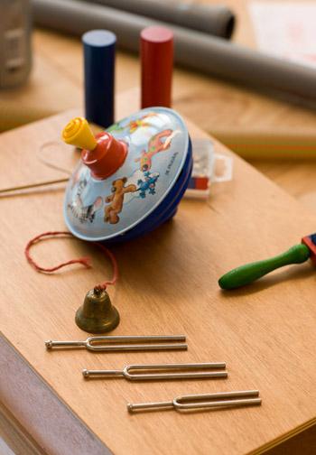 Auf dem Foto sind ist ein Kreisel aus Metall und Holzklötze sowie drei kleine Stimmgabeln aus Metall abgebildet.