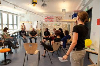 Eine Moderatorin blickt in einen Stuhlkreis, wo Studierende sitzen und dsikutieren.