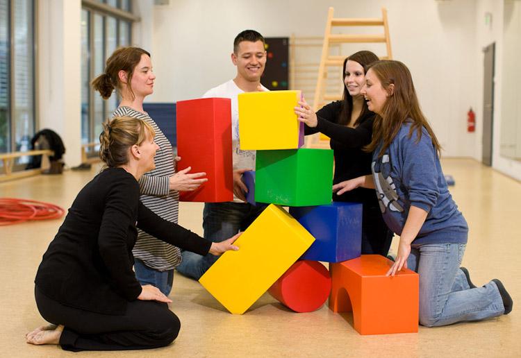 """Studierende bauen im Bewegungsraum eine """"Skulptur"""" aus großen farbigen Stoffwürfeln auf."""