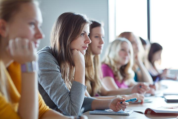 Unterrichtssituation: eine Reihe Studierender, Fokus auf eine junge Frau, die im Gegenlicht sitzt und nachdenklich nach vorne schaut.