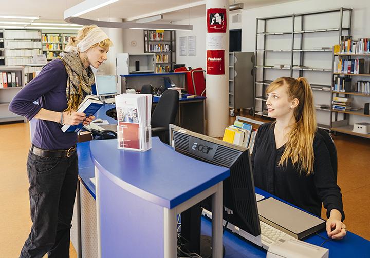 Am Tresen der Bibliothek: eine Studentin steht dafür und wird von einer Mitarbeiterin bedient.