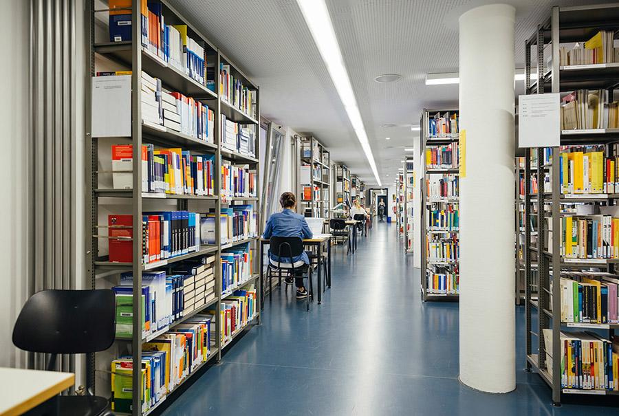 Blick durch die Bibliothek: links und rechts Bücherregale, in der Mitte ein Gang.