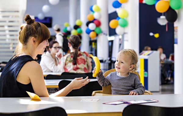 Eine Mutter sitzt mit ihrem Kind in der Mensa und gibt diesem gerade eine Banane