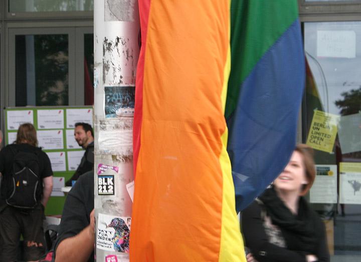 Detailansicht der Regenbogenflagge vor der ASH Berlin, dahinter verschwommen ein lachendes Gesicht