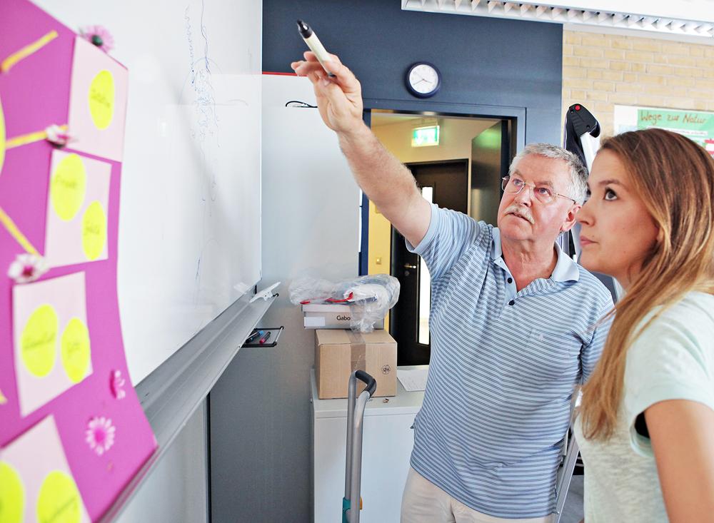Ein Prof erklärt einer Studentin ein Schaubild an der Tafel