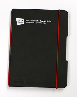 Das schicke, schwarze, handliche Notizbuch trägt das Logo der Hochschule. Es kann mit einem roten Gummiband verschlossen beziehungsweise zusammengehalten werden.