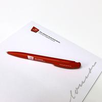 Auf dem Foto ist das Schreibset abgebildet, bestehend aus einem Notizblock und ASH Berlin Kugelschreiber.