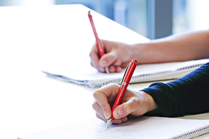 Aufnahme von zwei Händen mit Kugelschreiben, welche Mitschriften notieren.
