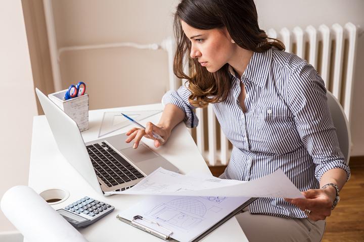 Eine Frau sitzt beschäftigt am Schreibtisch, wo sie Mitschriften mit einem Arbeitsdokument am Laptop abgleicht.