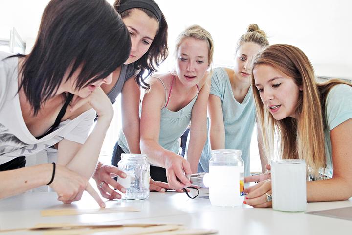 Eine Gruppe von Studentinnen sitzt am Tisch.
