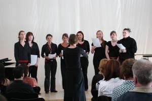Singing alice: Der Hochschulchor singt vor einem Publikum.