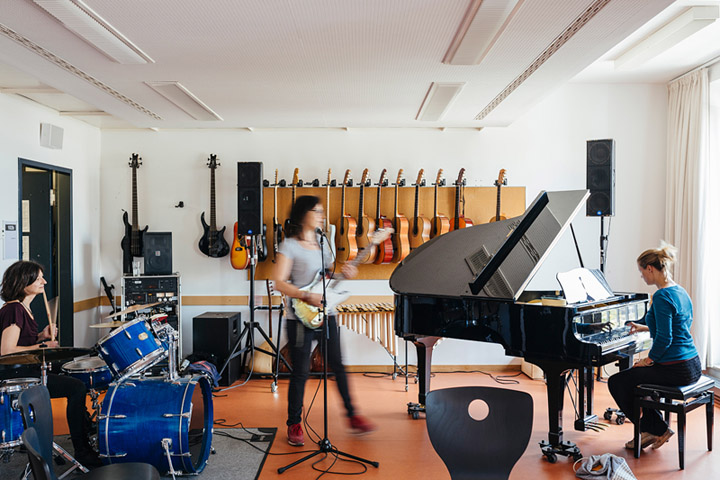 E-Gitarre, Schlagzeug und Flügel- eine Gruppe Studierender musiziert zusammen.