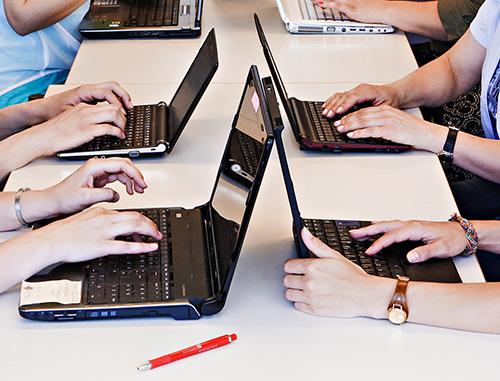 Detailansicht mehrerer Laptops, an denen gearbeitet wird.