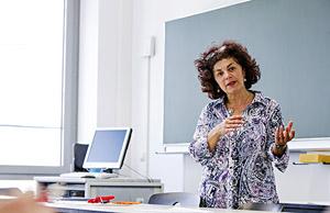 Eine Professorin steht vor der Tafel und erklärt etwas.