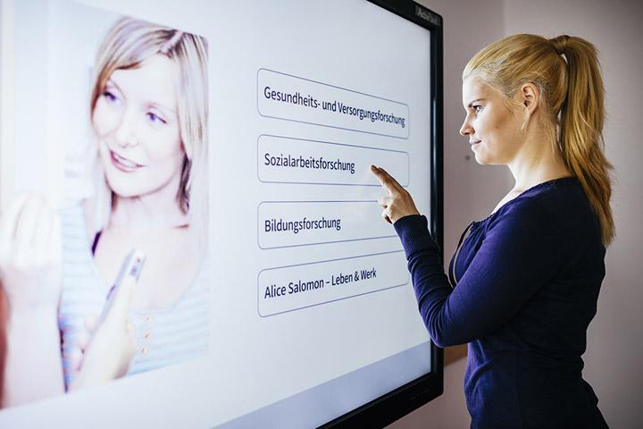 Eine Studierende steht vor einem riesigen Touchscreen, auf dem in einer Grafik die Forschungsschwerpunkte der ASH Berlin erscheinen: Gesundheits- und Versorgungsforschung, Sozialarbeitsforschung, Bildungsforschung, Alice Salomon – Leben & Werk.