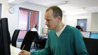 Mann sitzt vor einem Computer und macht sich Notizen