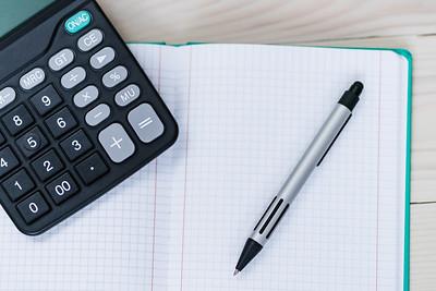 Kugelschreiber und Taschenrechner liegen auf einem aufgeklappten Notizbuch
