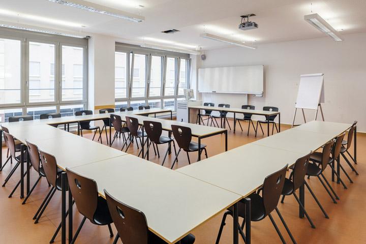 Ein Seminarraum der ASH Berlin mit Schreibtischen und Stühlen.