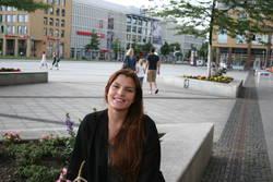 Andrea aus Spanien nimmt auf einer Bank vor der Hochschule Platz.