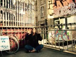 Dilan lässt sich vor einer mit Street Art verzierten Häuserecke fotografieren.