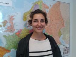 Maria aus Österreich steht vor einer großen Weltkarte im International Office.