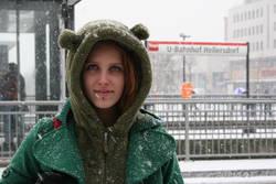 Spela aus Slowenien steht an einer verschneiten Haltestelle im winterlichen Berlin.