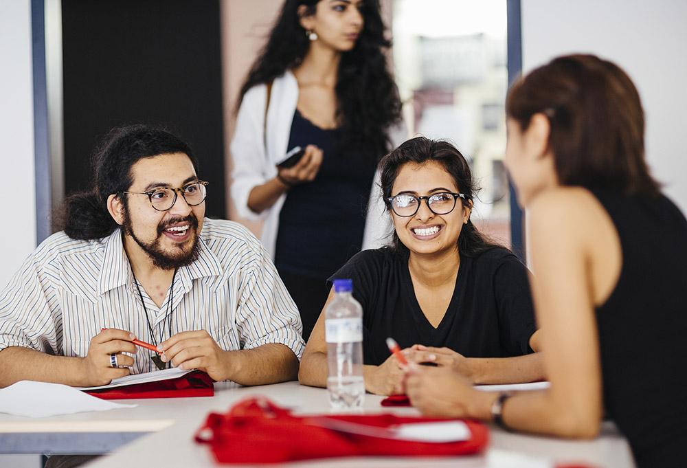 Drei Studierende sitzen an einem Tisch und unterhalten sich.