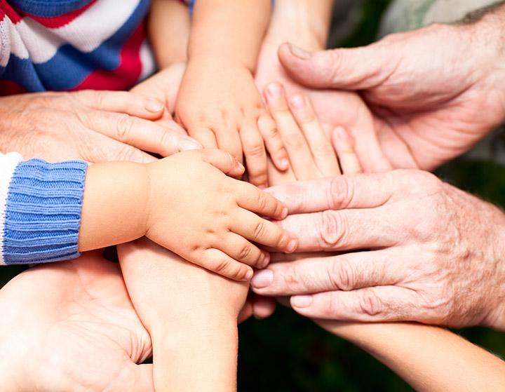 Junge und alte Menschen haben ihre Hände ausgestreckt und aufeinander gelegt.