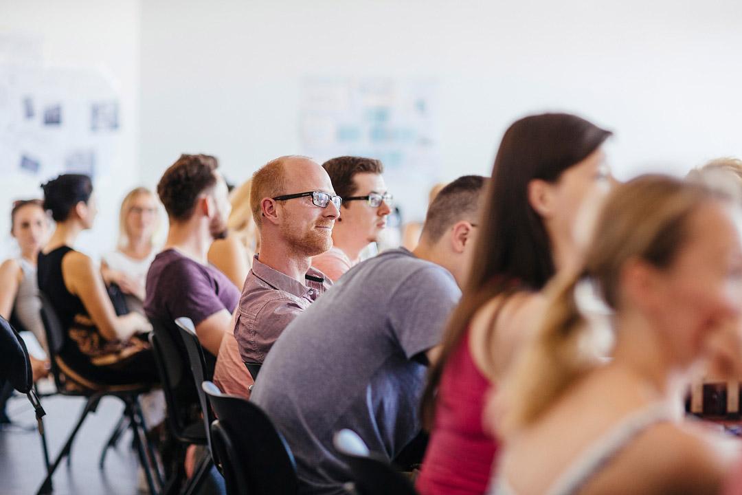 Lehrsituation: Eine Reihe Studierender im Unterricht, Fokus auf einen Studenten mit Brille, der lächeln zuhört