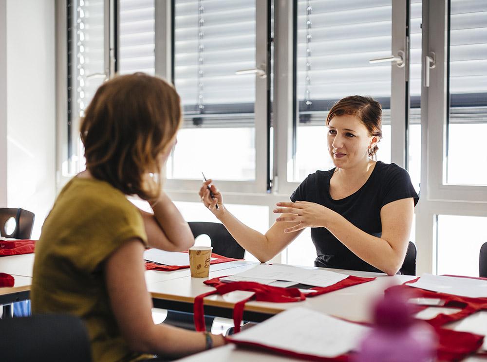 Zwei Studentinnen sitzen sich an einem Tisch gegenüber. Eine Studentin erklärt der anderen etwas und gestikuliert mit ihren Armen.
