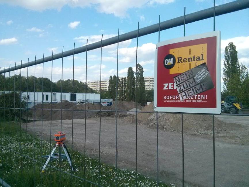 """Ein in Hellersdorf aufgenommenes Foto zeigt einen Bauzaun, an welchem Nazis ein Aufkleber angebracht haben mit der Aufschrift: """"Nein zum Heim""""."""