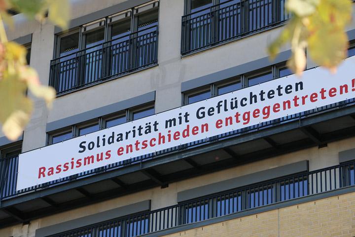 """Banner an der Hausfront der ASH Berlin: """"Solidarität mit Geflüchtete. Rassismus entschieden entgegentreten!"""