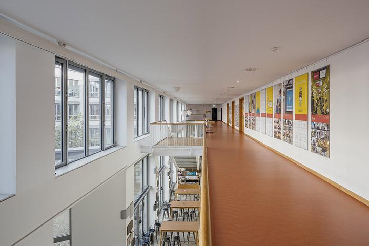 Blick über einen Flur der ASH Berlin, an der Wand hängen bunte Poster