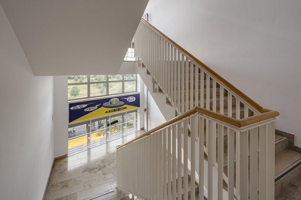 Blick in ein Treppenhaus der ASH Berlin: quer entlang einer großen Fensterfront hängt ein Bild, auf dem ein Ufo abgebildet ist, das gerade auf einer stilisierten Mondlandschaft landet.