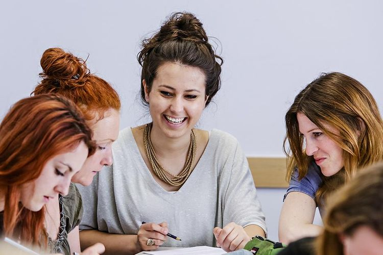 Drei Studentinnen des Master of Arts Studiengangs Biografisches und Kreatives Schreiben sitzen an einem Tisch und machen Notizen.