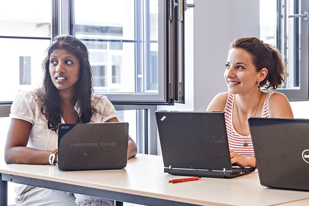 Vergrößern: Zwei Studentinnen sitzen am Tisch und schauen aufmerksam nach vorne.