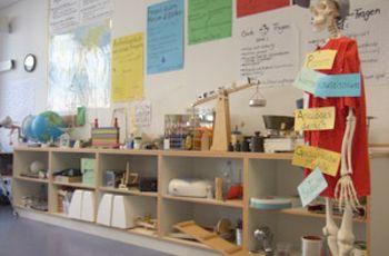 Blick in die Lernwerkstatt, Regale mit Experimentiergeräten, auf der rechten Seite ein Skelett mit Mantel und Schirmmütze.