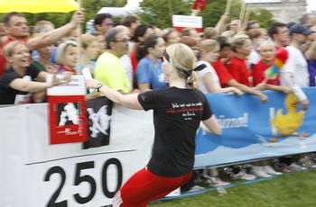 Eine Läuferin des ASH Berlin Teams wird von der Menschenmenge hinter der Bande angefeuert.