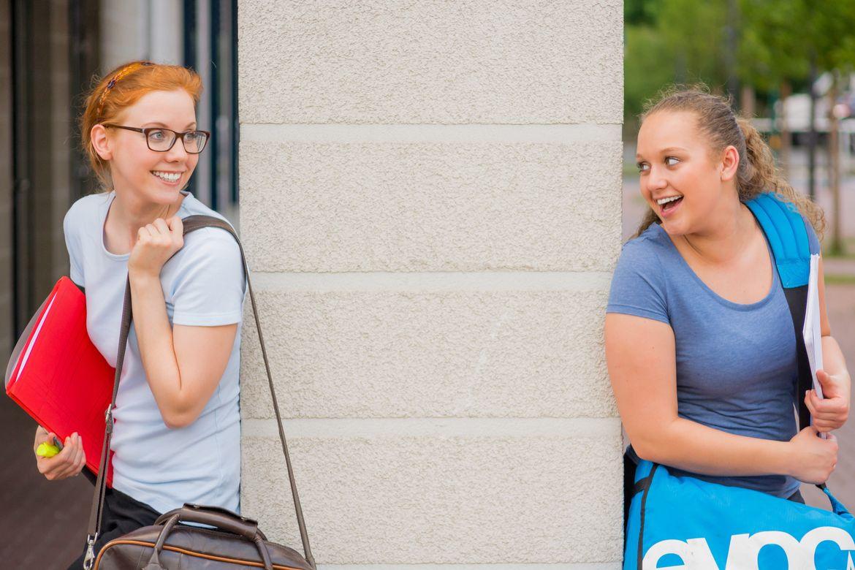 Zwei junge Frauen lehnen an einer Säule und lächeln sich verschmitzt an.