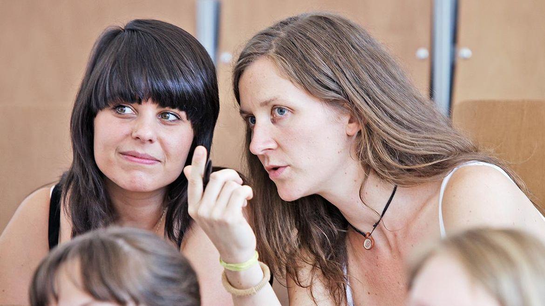 Zwei Studentinnen im Hörsaal, die eine flüstert der anderen etwas ins Ohr