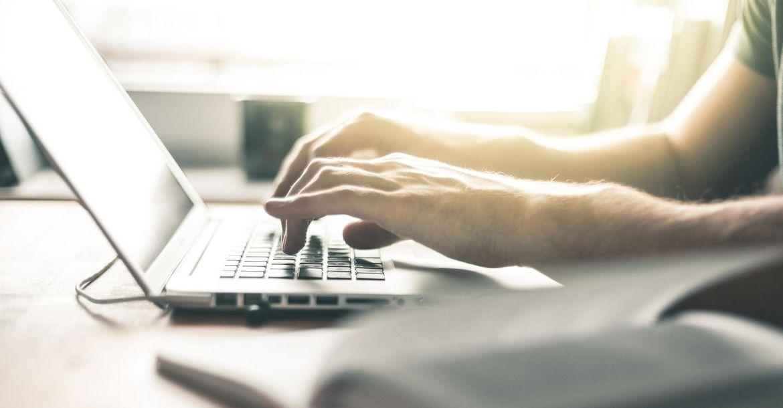 Die Hände einer Person tippen auf der Tastatur eines Laptops. Im Vordergrund liegt ein Buch.
