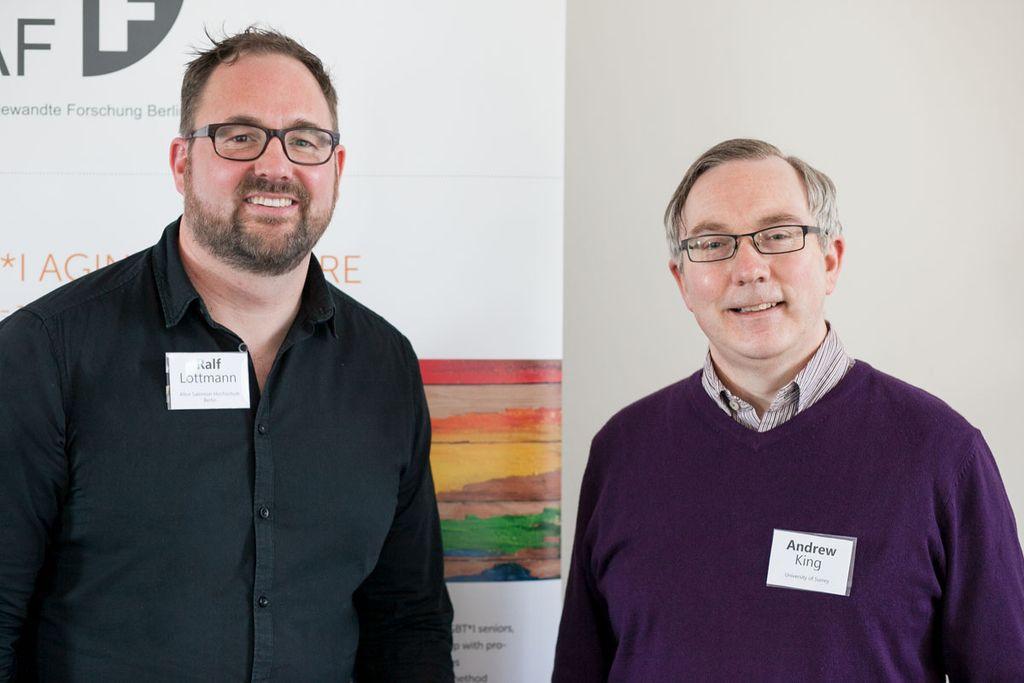 Vergrößern: Zwei männliche Wissenschaftler stehen vor einem Plakat und lächeln in die Kamera