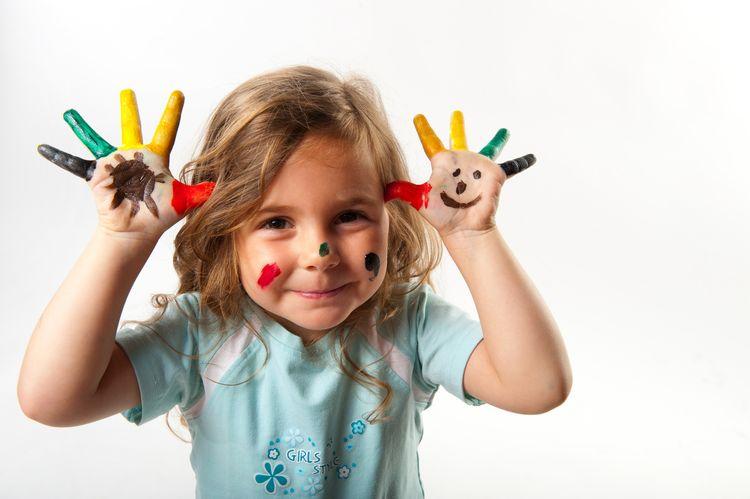 Lachendes Mädchen zeigt Hände mit bunten Fingermalfarben dies nimmt Bezug auf Master of Arts Studiengang Dialogische Qualitätsentwicklung in den Frühen Hilfen und im Kinderschutz