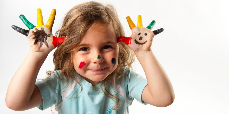 Lachendes Mädchen zeigt Hände mit bunten Fingermalfarben