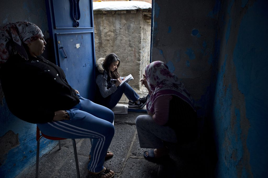 Vergrößern: Die Wissenschaftlerin Begüm Basdas interviewt zwei Frauen und macht sich im Sitzen Notizen