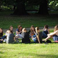 Studentinnen sitzen im Kreis auf einer Wiese