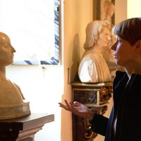Eine weiße Büste und rechts daneben Julia Franz mit kurzen blonden Haaren, die auf die Büste schaut